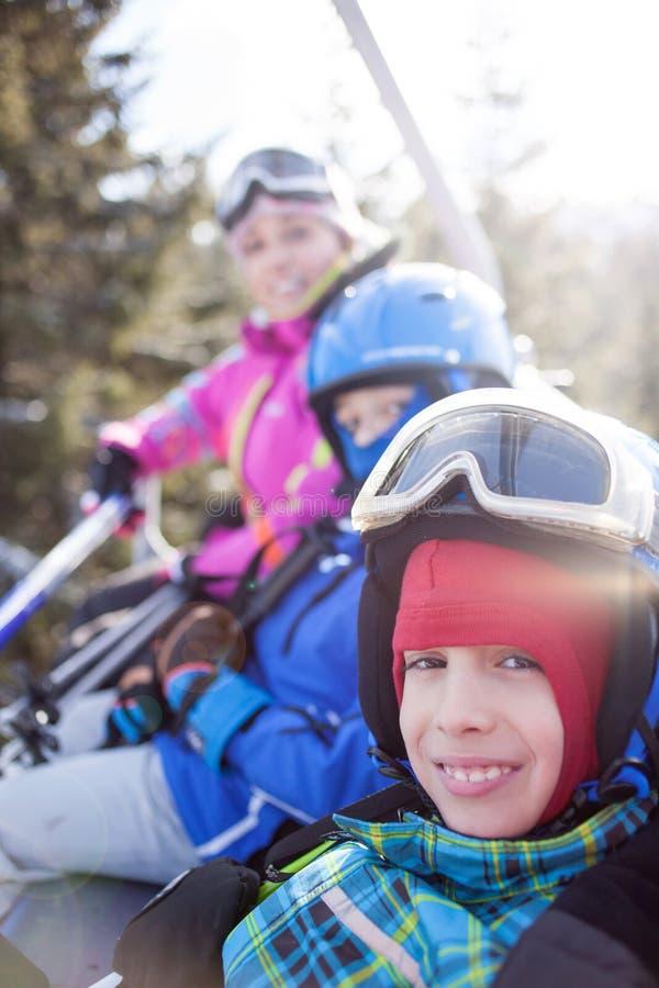 Den lyckliga familjen skidar laggyckel på det härliga berget royaltyfri foto