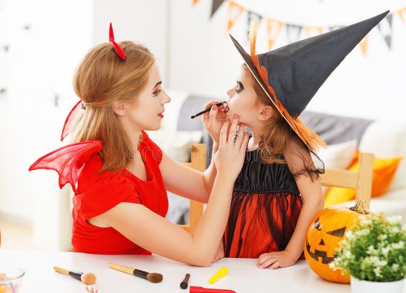 Den lyckliga familjen som får klar för halloween, gör smink royaltyfria bilder