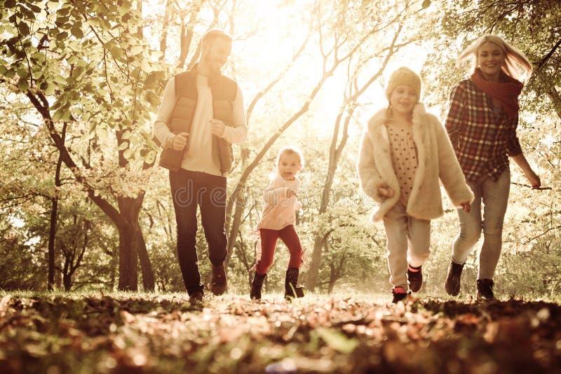 Den lyckliga familjen som går ho, parkerar samman med öppna armar arkivfoto