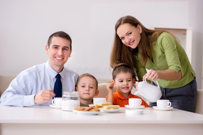 Den lyckliga familjen som har frukosten tillsammans hemma arkivbild