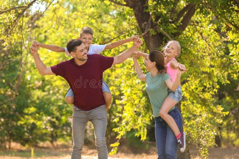 Den lyckliga familjen som har gyckel parkerar in royaltyfri bild