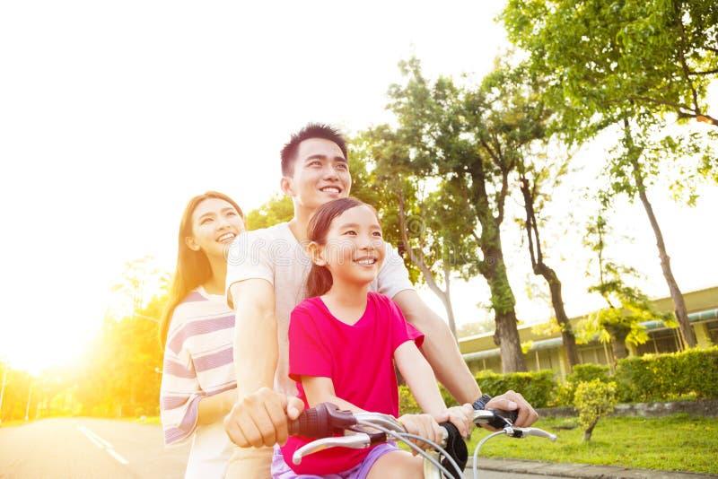 Den lyckliga familjen som har gyckel parkerar in, med cykeln fotografering för bildbyråer