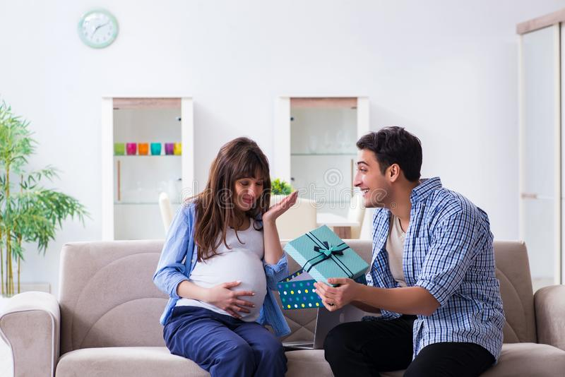 Den lyckliga familjen som hemma firar havandeskap royaltyfri foto