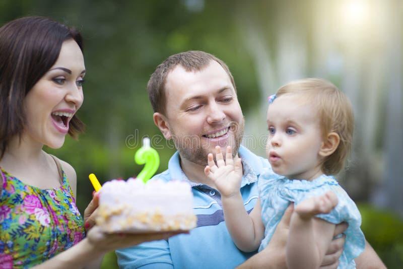 Den lyckliga familjen som i andra hand firar födelsedag av, behandla som ett barn dottern arkivbilder