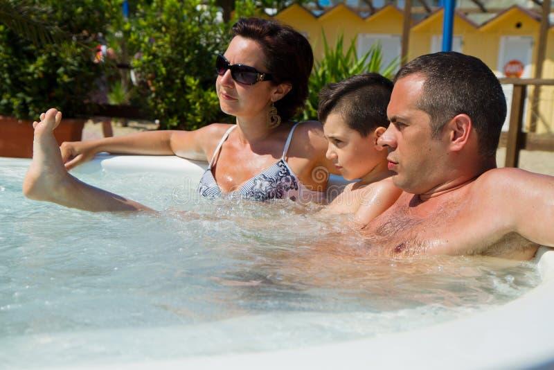 Den lyckliga familjen som kopplar av i varmt, badar semester arkivfoton