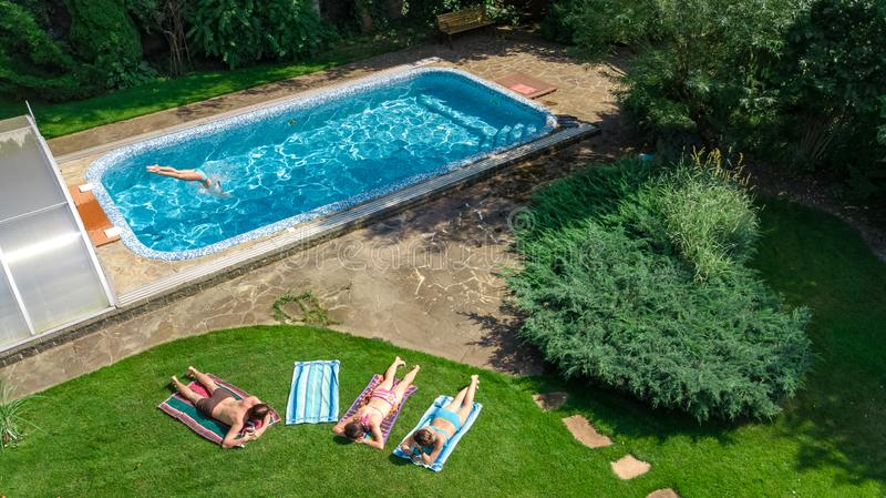 Den lyckliga familjen som kopplar av vid simbassängen, den flyg- surrsikten från över av föräldrar och ungar har gyckel på semest arkivfoton