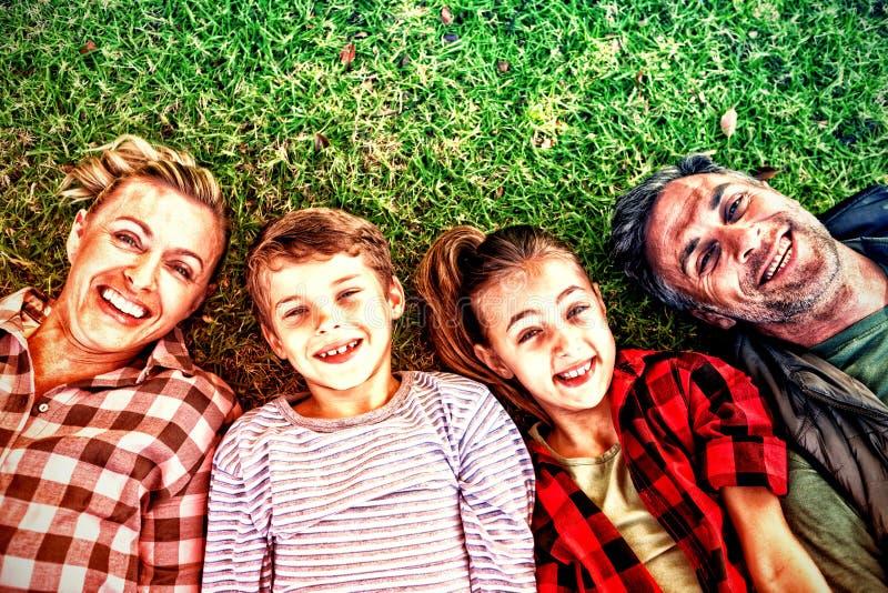 Den lyckliga familjen som ligger på gräset parkerar in arkivbild