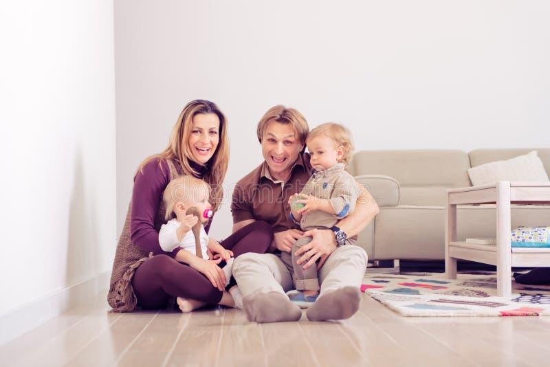 Den lyckliga familjen som sitter på golv med deras litet, behandla som ett barn familjen som hemma spenderar tid med deras son oc arkivfoton