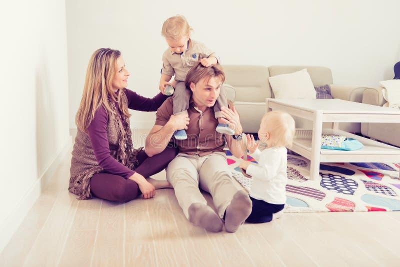 Den lyckliga familjen som sitter på golv med deras litet, behandla som ett barn familjen som hemma spenderar tid med deras son oc royaltyfri bild