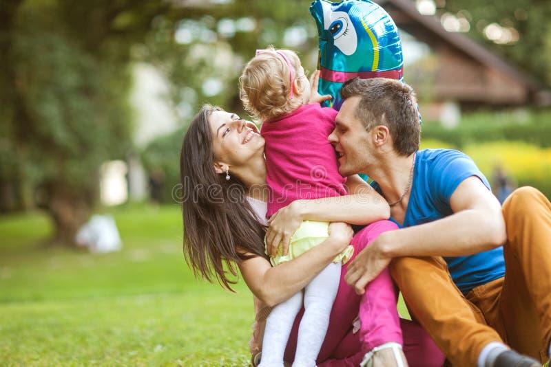 Den lyckliga familjen som in spelar, parkerar med dottern arkivbild