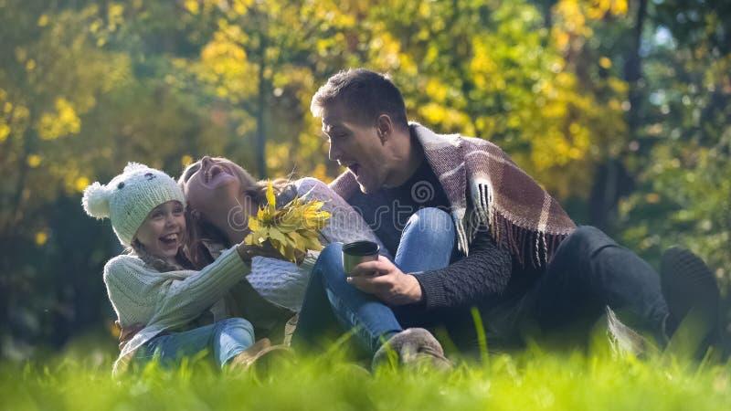 Den lyckliga familjen som spenderar tid i höst, parkerar, har picknick tillsammans det fria och att ha gyckel royaltyfria foton