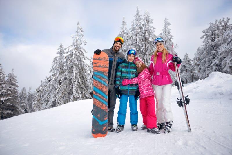 Den lyckliga familjen som tycker om i vinter, semestrar tillsammans royaltyfri foto