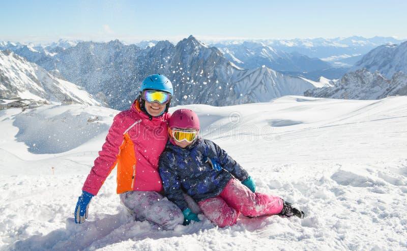 Den lyckliga familjen som tycker om vinter, semestrar i berg royaltyfri fotografi