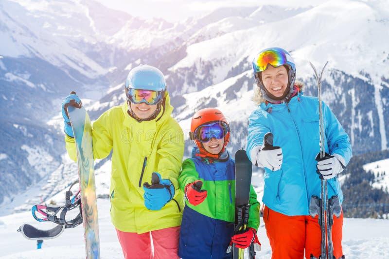 Den lyckliga familjen som tycker om vinter, semestrar i berg , Skidar solen, snö och gyckel fotografering för bildbyråer
