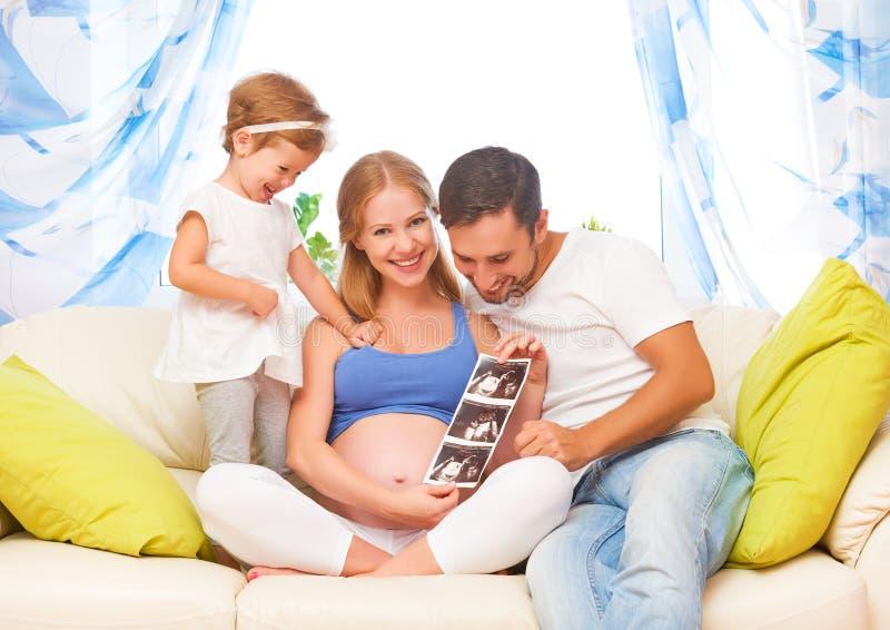Den lyckliga familjen som väntar på, behandla som ett barn se gravid mamma för ultraljudet, D royaltyfri bild