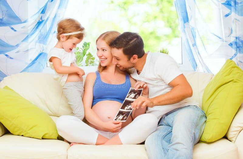 Den lyckliga familjen som väntar på, behandla som ett barn se gravid mamma för ultraljudet, D arkivfoton