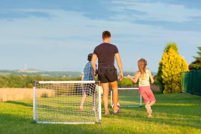 Den lyckliga familjen spelar fotboll i sommar fotografering för bildbyråer