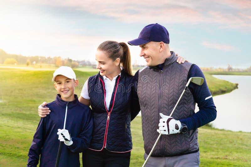 Den lyckliga familjen spelar golf i höst royaltyfria bilder