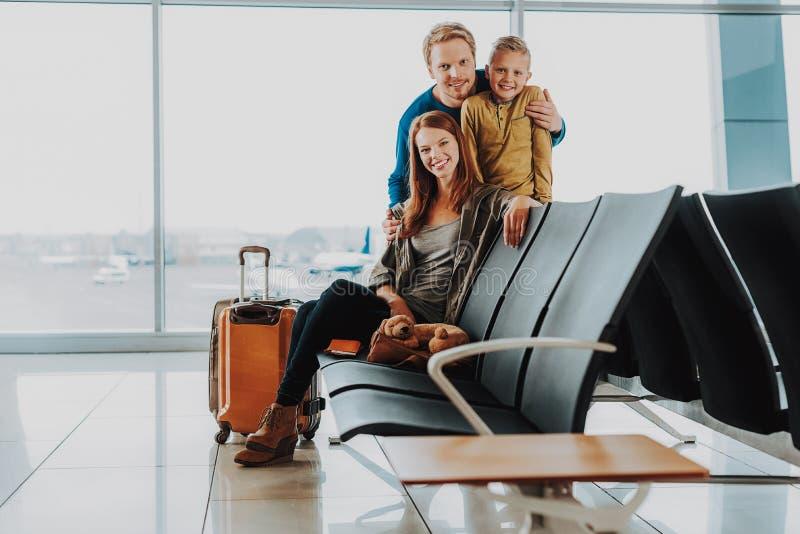 Den lyckliga familjen spenderar tid tillsammans på flygplatsen royaltyfri foto