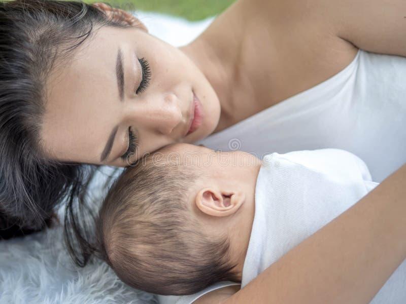 Den lyckliga familjen, stående av den härliga unga asiatiska modern som kysser hennes nyfött, behandla som ett barn med förälskel arkivfoto