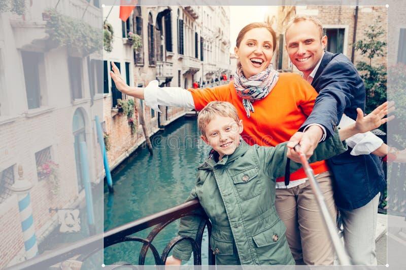 Den lyckliga familjen tar ett sj?lvfoto p? det av broar i Venedig royaltyfri bild