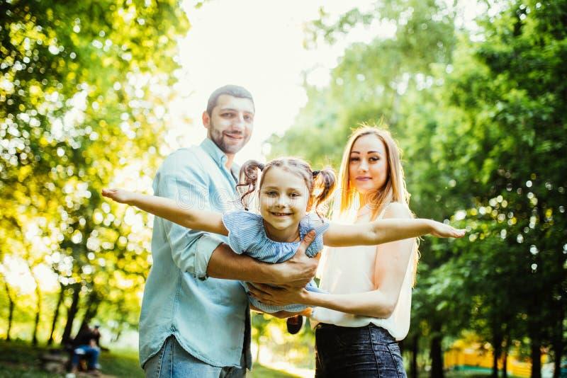 Den lyckliga familjen tycker om sommar i grön sommar parkerar royaltyfri fotografi
