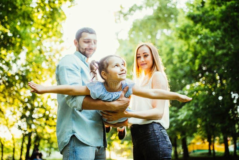 Den lyckliga familjen tycker om sommar i grön sommar parkerar arkivbilder