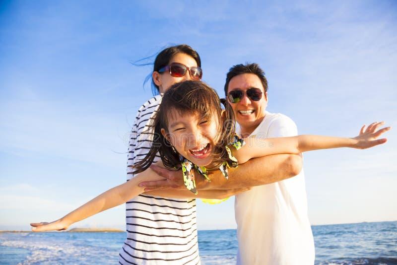 Den lyckliga familjen tycker om sommarsemester på stranden royaltyfri foto