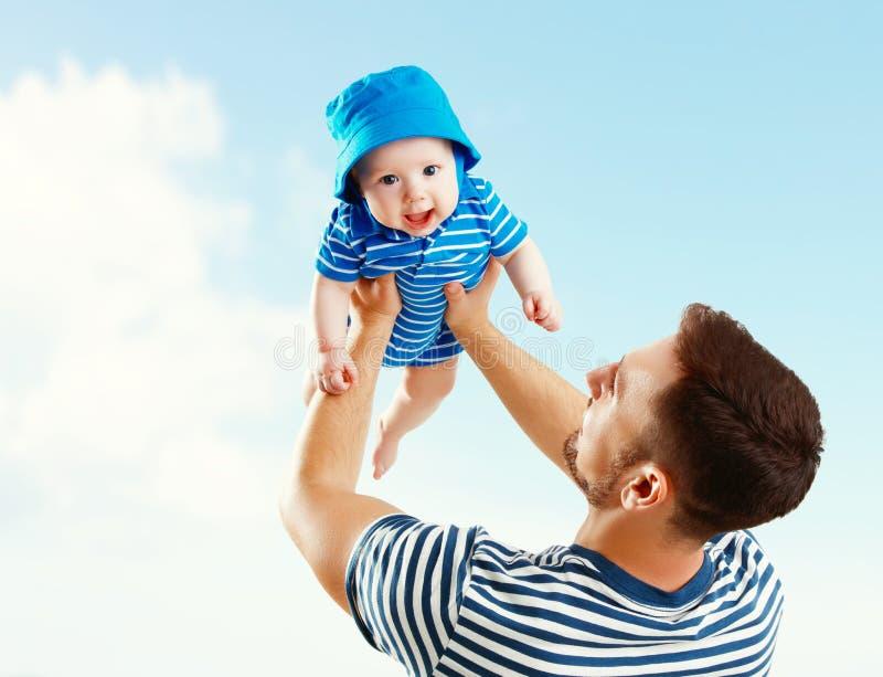 Den lyckliga familjfadern kastar behandla som ett barn upp sonen på himmel royaltyfri fotografi