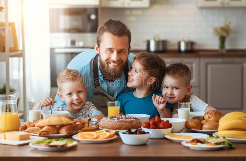 Den lyckliga familjfadern med barn matar hans söner och dotter i kök med frukosten fotografering för bildbyråer