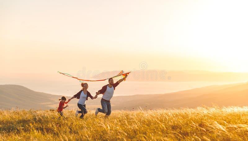 Den lyckliga familjfadern, modern och barndottern lanserar på en drake royaltyfri foto