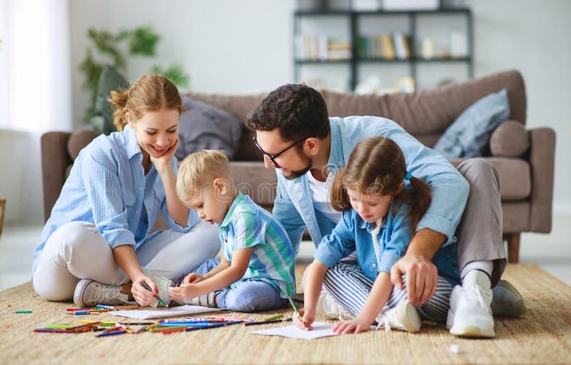 Den lyckliga familjmoderfadern och ungar drar tillsammans hemma royaltyfri foto
