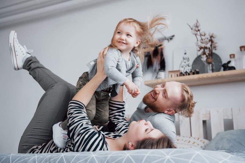 Den lyckliga familjmodern, fadern och barndottern skrattar i säng royaltyfria foton