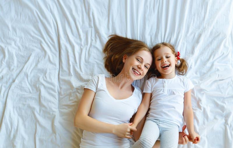 Den lyckliga familjmodern och barndottern skrattar i säng royaltyfri fotografi