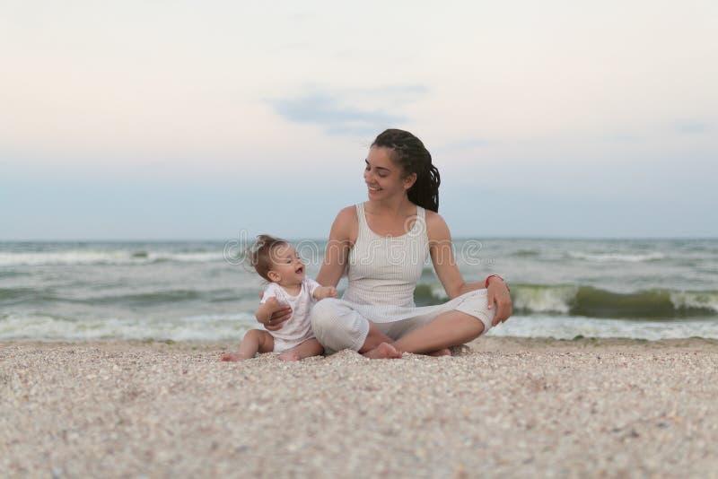 Den lyckliga familjmodern och barndottern som gör yoga, mediterar i lotusblommaposition på stranden på solnedgången royaltyfria bilder