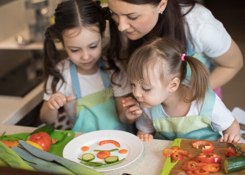 Den lyckliga familjmodern och barnflickan förbereder sund mat, dem improviserar tillsammans i köket arkivbild