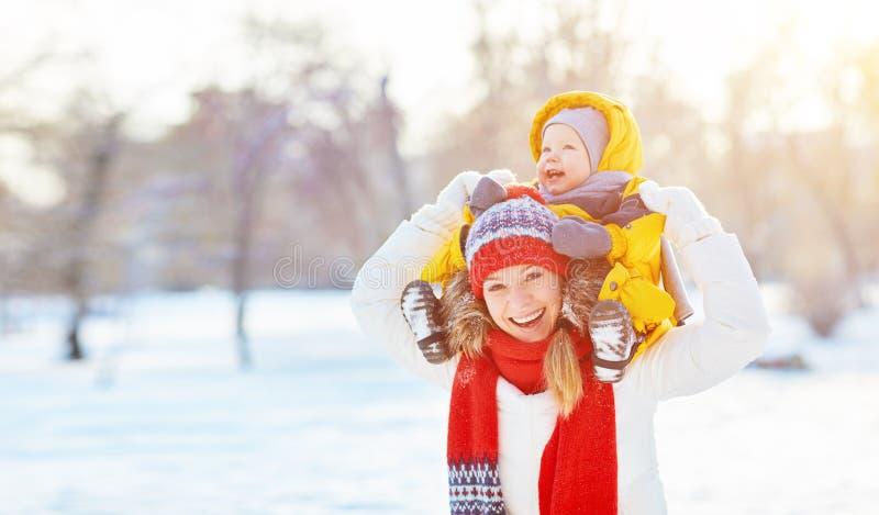 Den lyckliga familjmodern och behandla som ett barn är lycklig att snö på vinter går royaltyfria foton