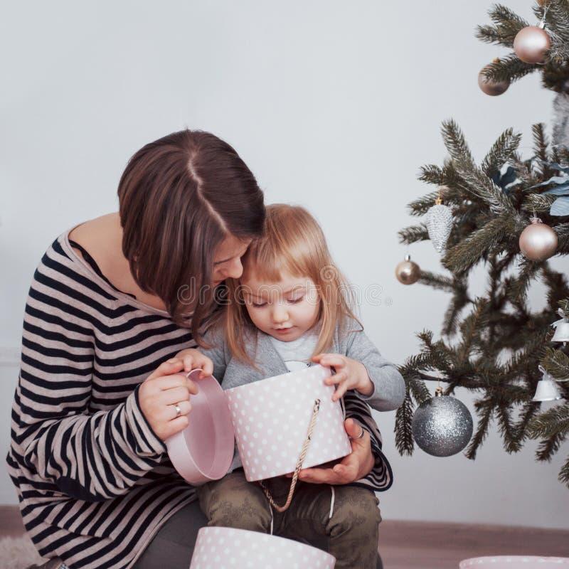 Den lyckliga familjmodern och behandla som ett barn dekorerar julgranen arkivbilder