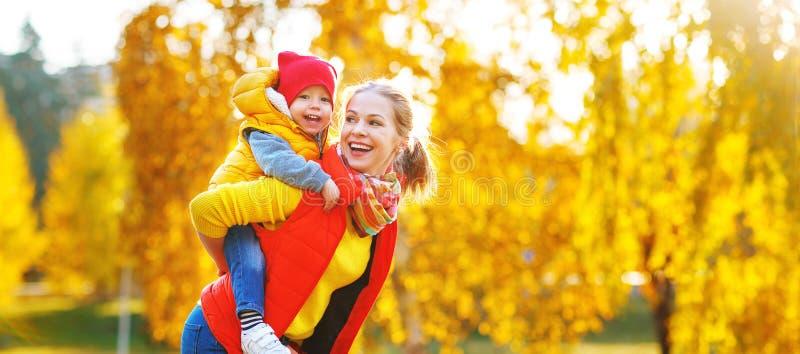 Den lyckliga familjmodern och behandla som ett barn sonen på höst går royaltyfri fotografi
