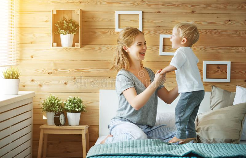 Den lyckliga familjmodern och behandla som ett barn sonlilla barnet som skrattar i säng royaltyfri fotografi