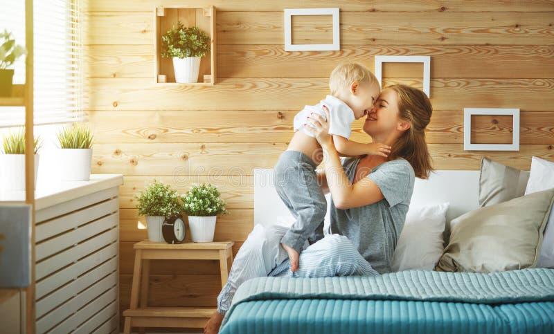 Den lyckliga familjmodern och behandla som ett barn sonlilla barnet som skrattar i säng royaltyfri foto