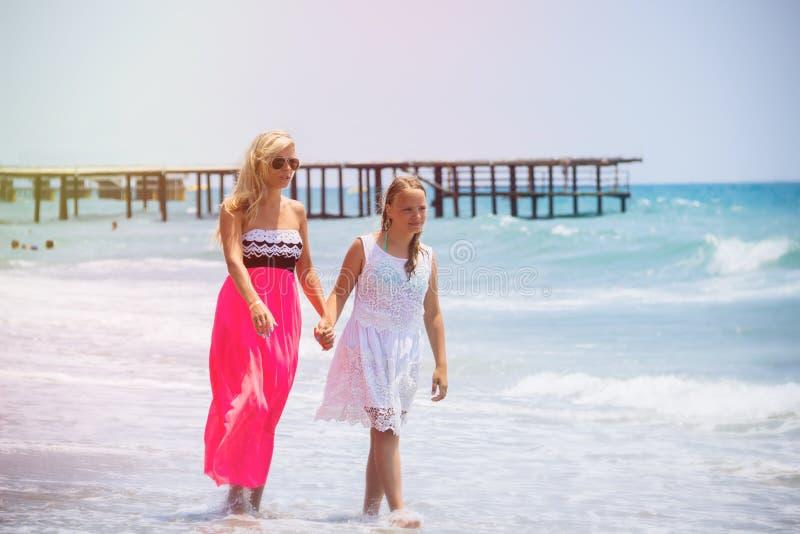 Den lyckliga familjmodern och tonåringdottern går, skrattar och spelar på stranden arkivfoton