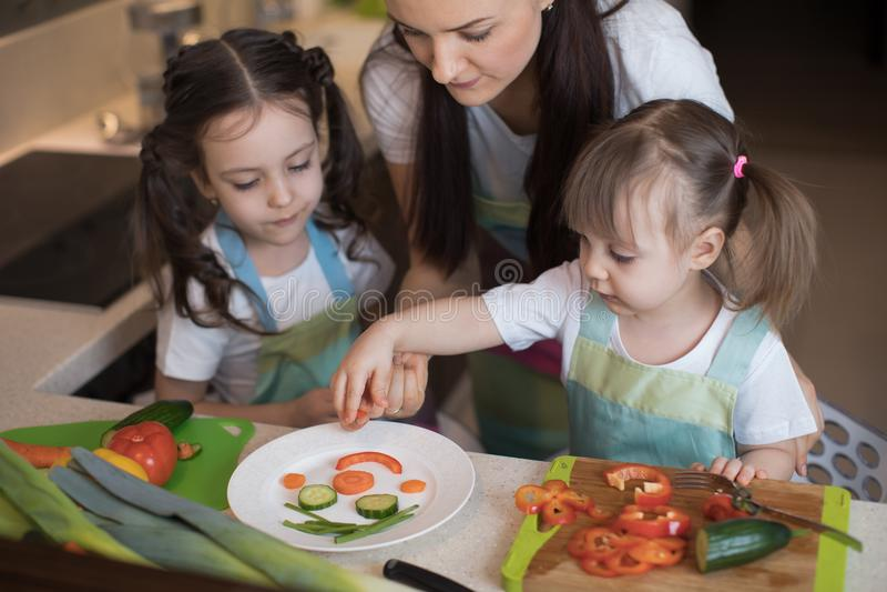 Den lyckliga familjmodern och ungar förbereder sund mat, dem improviserar tillsammans i köket arkivfoton