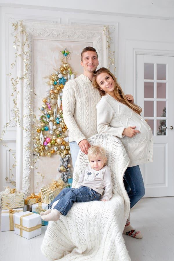 Den lyckliga familjståenden i hem - avla, den gravida modern och deras lilla son lyckligt nytt år julen dekorerade treen fotografering för bildbyråer