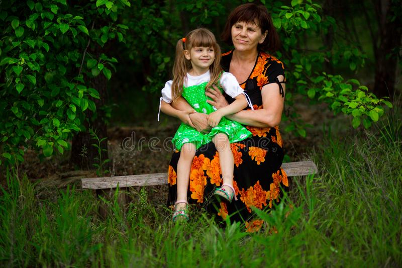 Den lyckliga farmodern och litet sondottersammanträde parkerar in royaltyfri bild