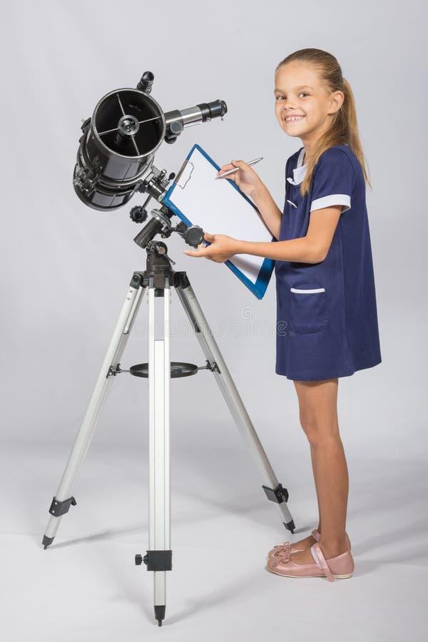 Den lyckliga flickaastronomen ser lycklig i bildanseende bredvid teleskopet arkivfoton