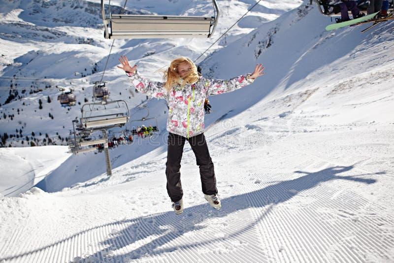Den lyckliga flickabanhoppningen på berg skidar lutningen royaltyfri fotografi