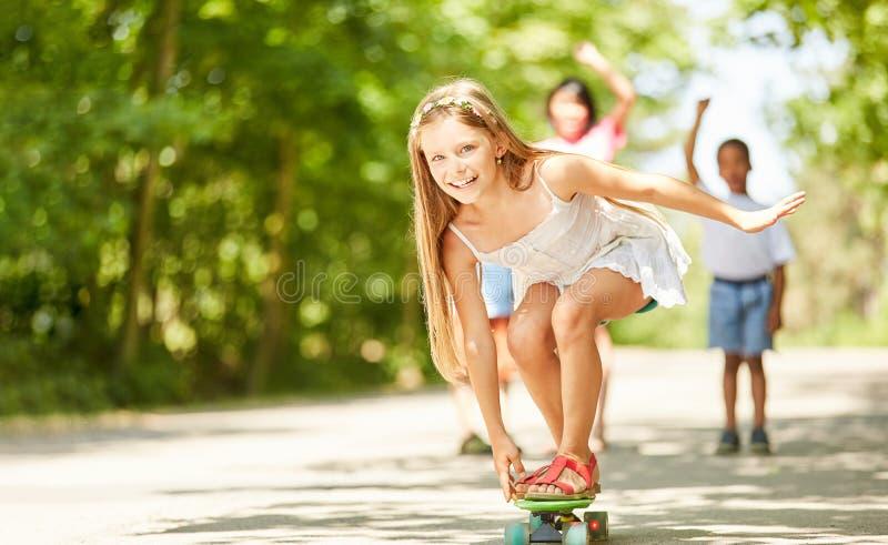 Den lyckliga flickan balanserar på skateboarden arkivfoton