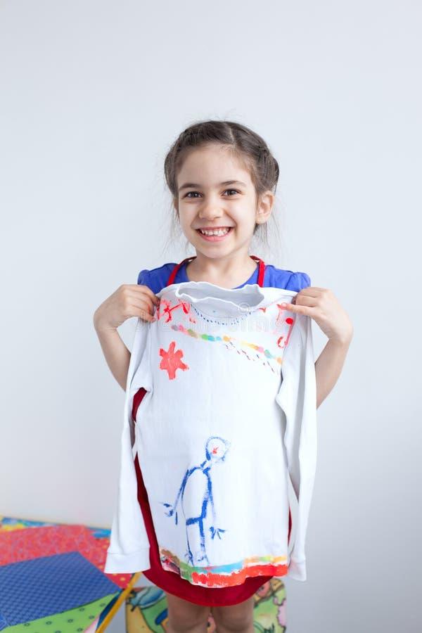 Den lyckliga flickan, barn med den vita designen dekorerade blusen arkivfoton