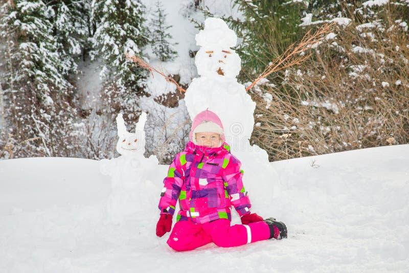 Den lyckliga flickan för det härliga barnet som plaing med en snögubbe på snöig vinter, går arkivbild